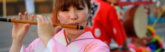 A young JApanese girl in traditional outfit playingg flute during festival. Fukuoka, Japan, East Asia.